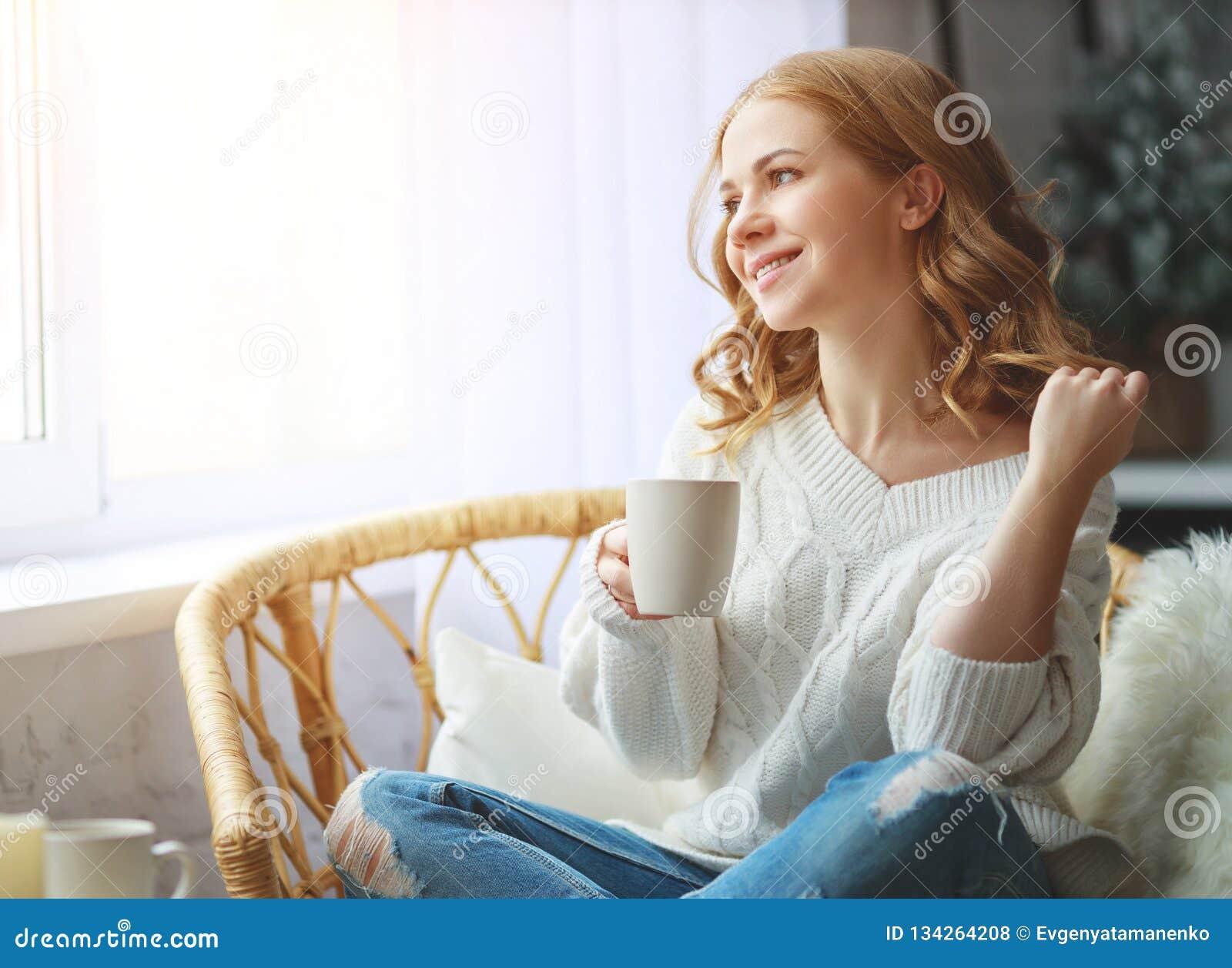 Gelukkige jonge vrouw het drinken ochtendkoffie door venster in de winter