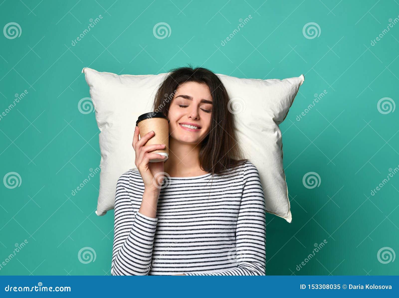 Gelukkige jonge vrouw met een kop van koffie of thee in haar handen, dromen op een hoofdkussen over om het even wat