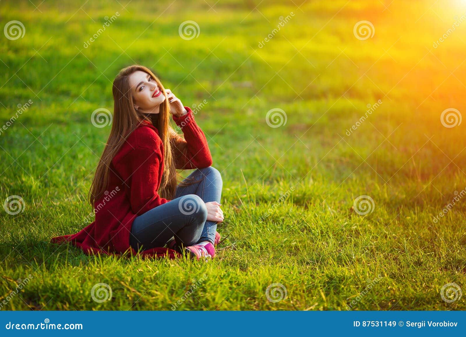 Gelukkige jonge vrouw Mooi wijfje die met lang gezond haar zon van licht in parkzitting genieten op groen gras De lente