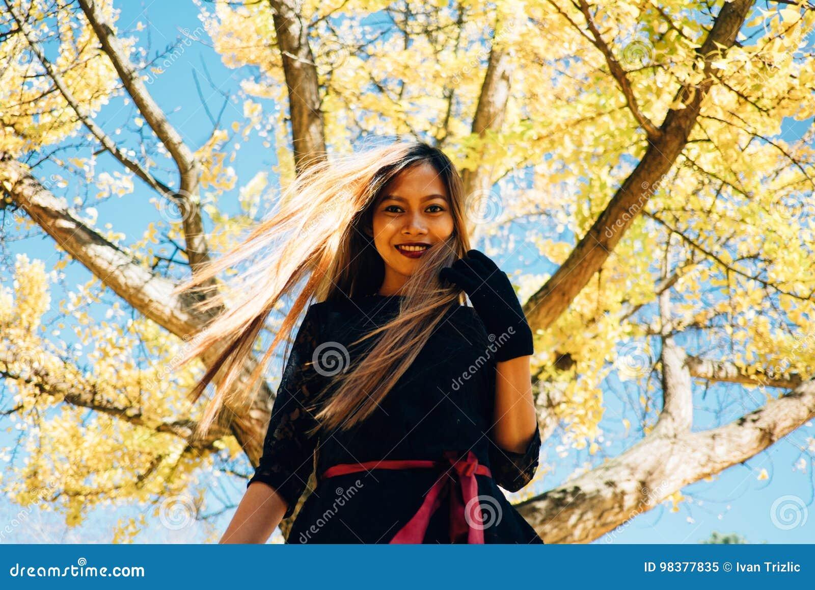 Gelukkige jonge vrouw in park op zonnige de herfstdag, het glimlachen Vrolijk mooi meisje in zwarte retro de manierstijl van de k