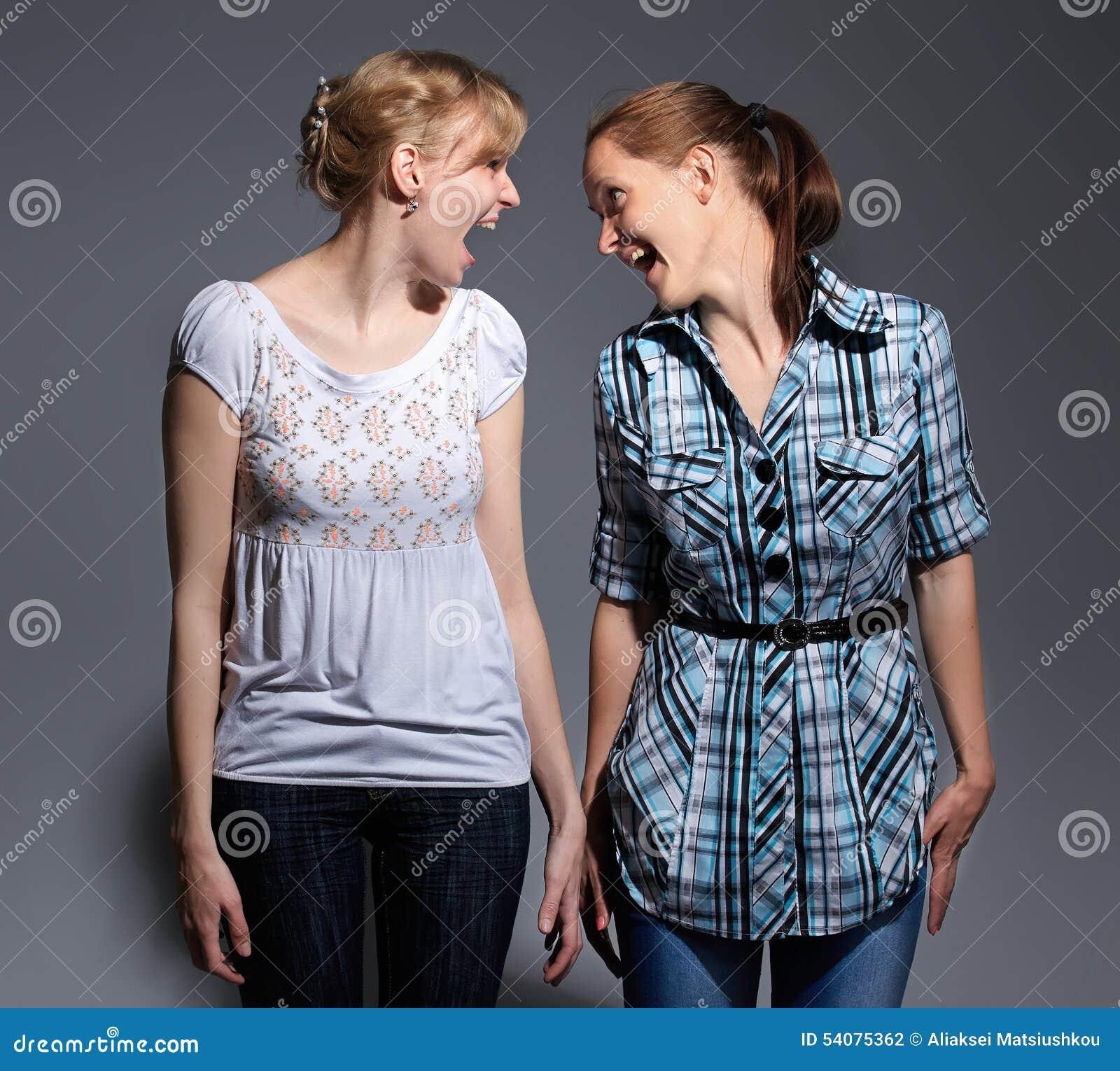 Gelukkige jonge vrouw twee die zich op grijze achtergrond bevinden