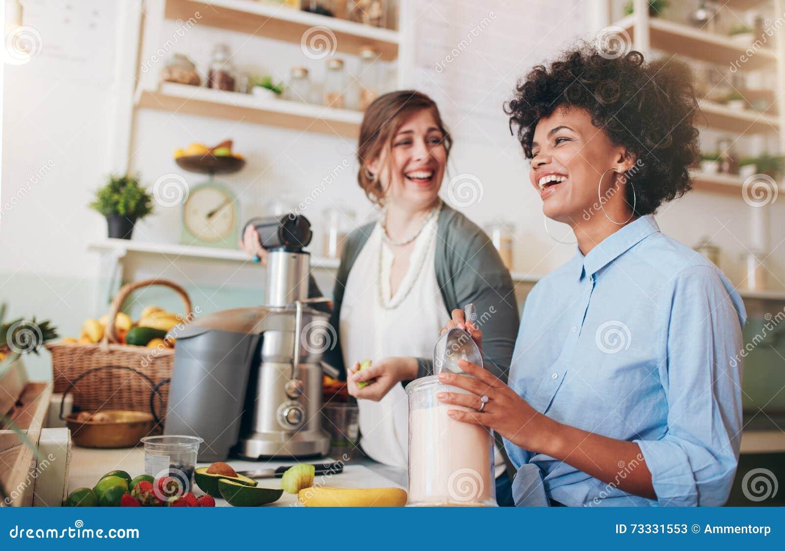 Gelukkige jonge vrouwen die bij de teller van de sapbar werken