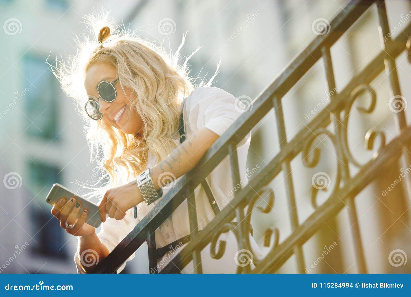 Gelukkige jonge vrouwenglimlachen en mededeling over telefoon over straat