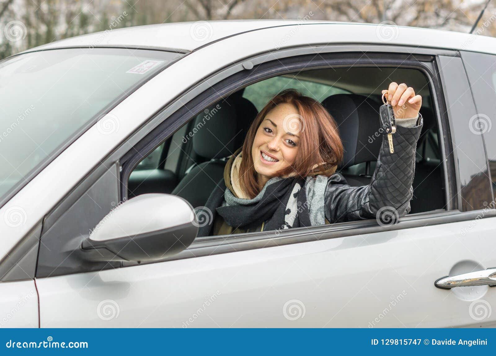 Gelukkige jonge vrouwenzitting in de auto die bij de camera glimlachen die de sleutel tonen