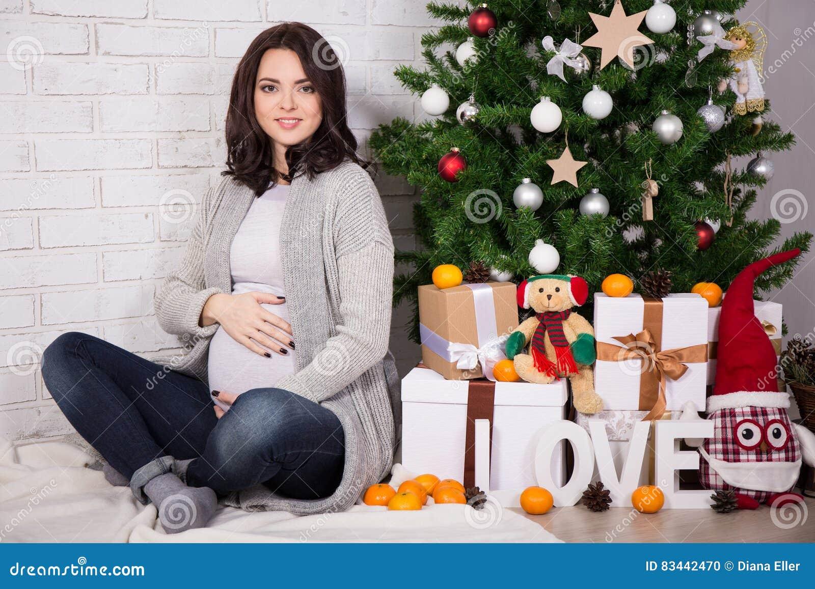 Gelukkige jonge zwangere vrouw met Kerstmisboom