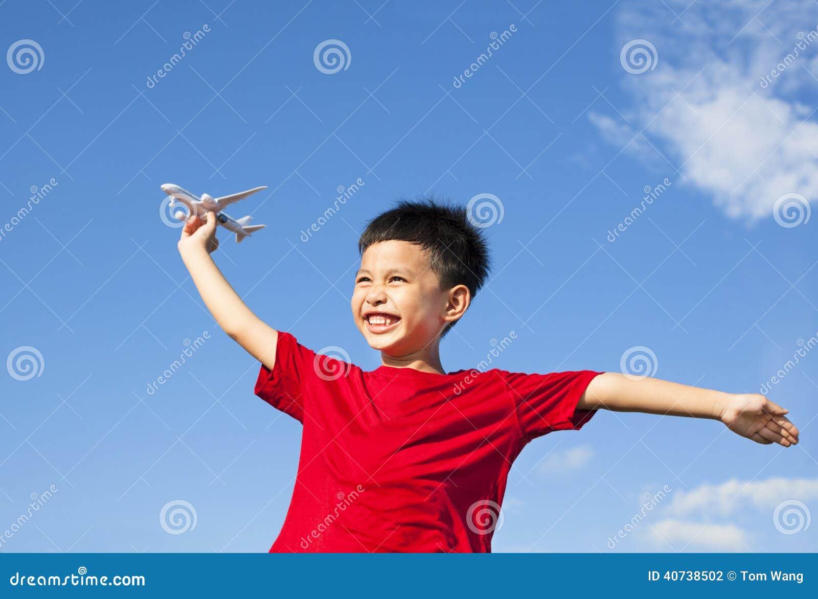 Gelukkige jongen die een vliegtuigstuk speelgoed met blauwe hemel houden