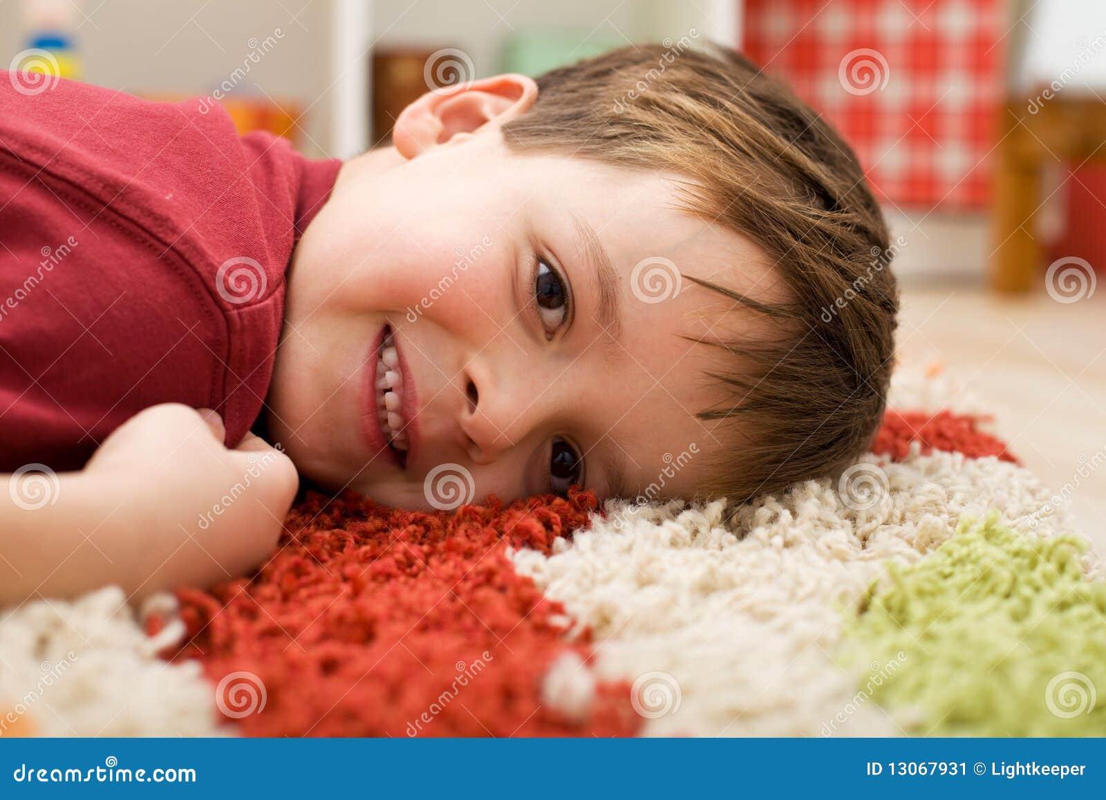 Gelukkige jongen die op een deken legt