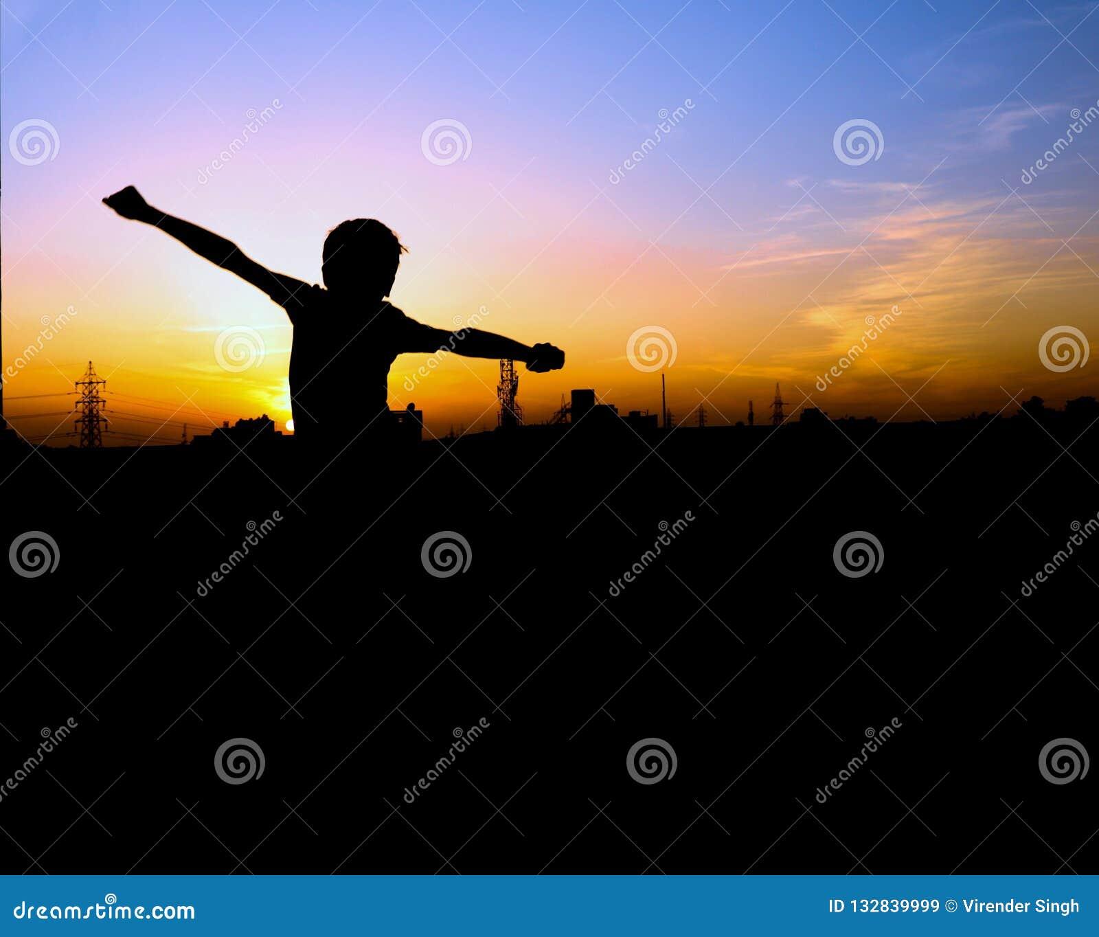 Gelukkige jongen die voor zonsondergang, mensensilhuette springen