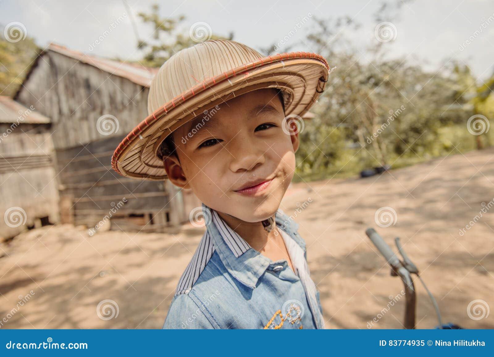 Gelukkige jongen met hoed op de landelijke straat in Vietnam