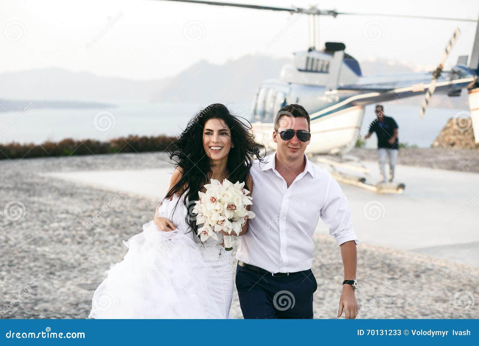 Gelukkige jonggehuwden dichtbij de helikopter