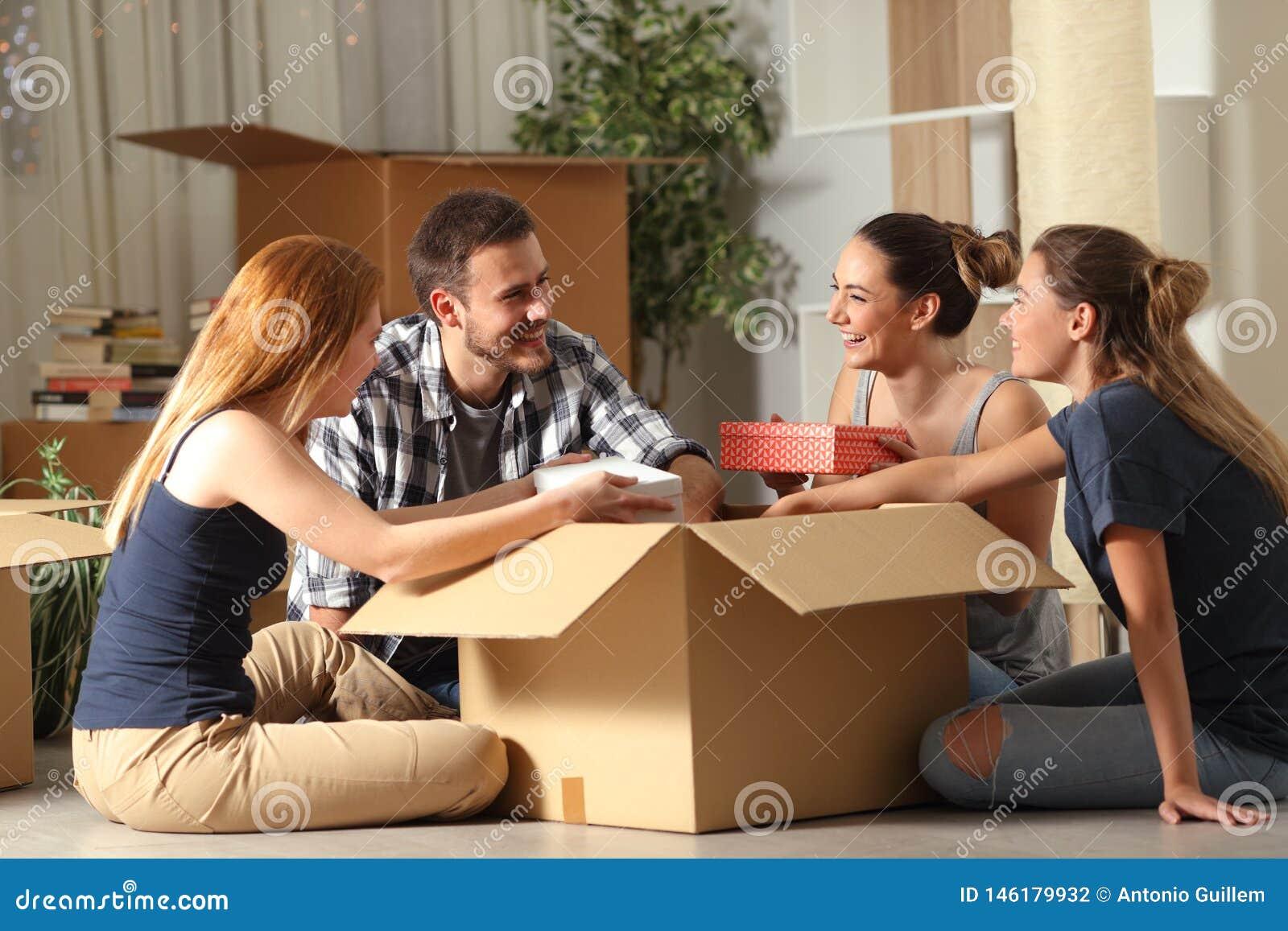 Gelukkige kamergenoten die bezittingen unboxing die zich naar huis bewegen