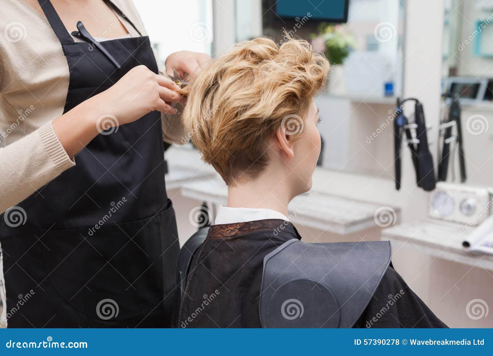 Gelukkige kapper die een klantenhaar snijden