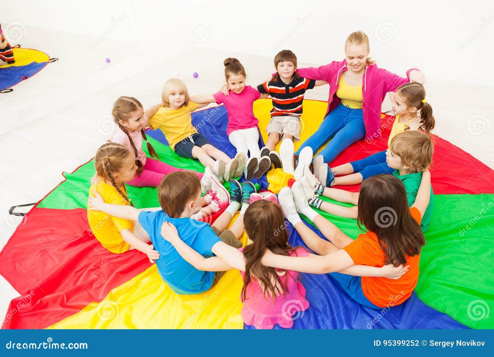 Gelukkige kinderen die cirkelspelen met leraar spelen