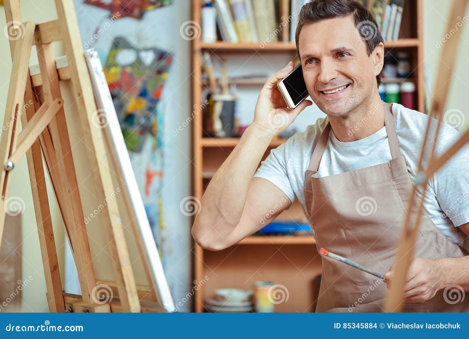 Gelukkige kunstenaar die op cellphone in het schilderen van studio spreken