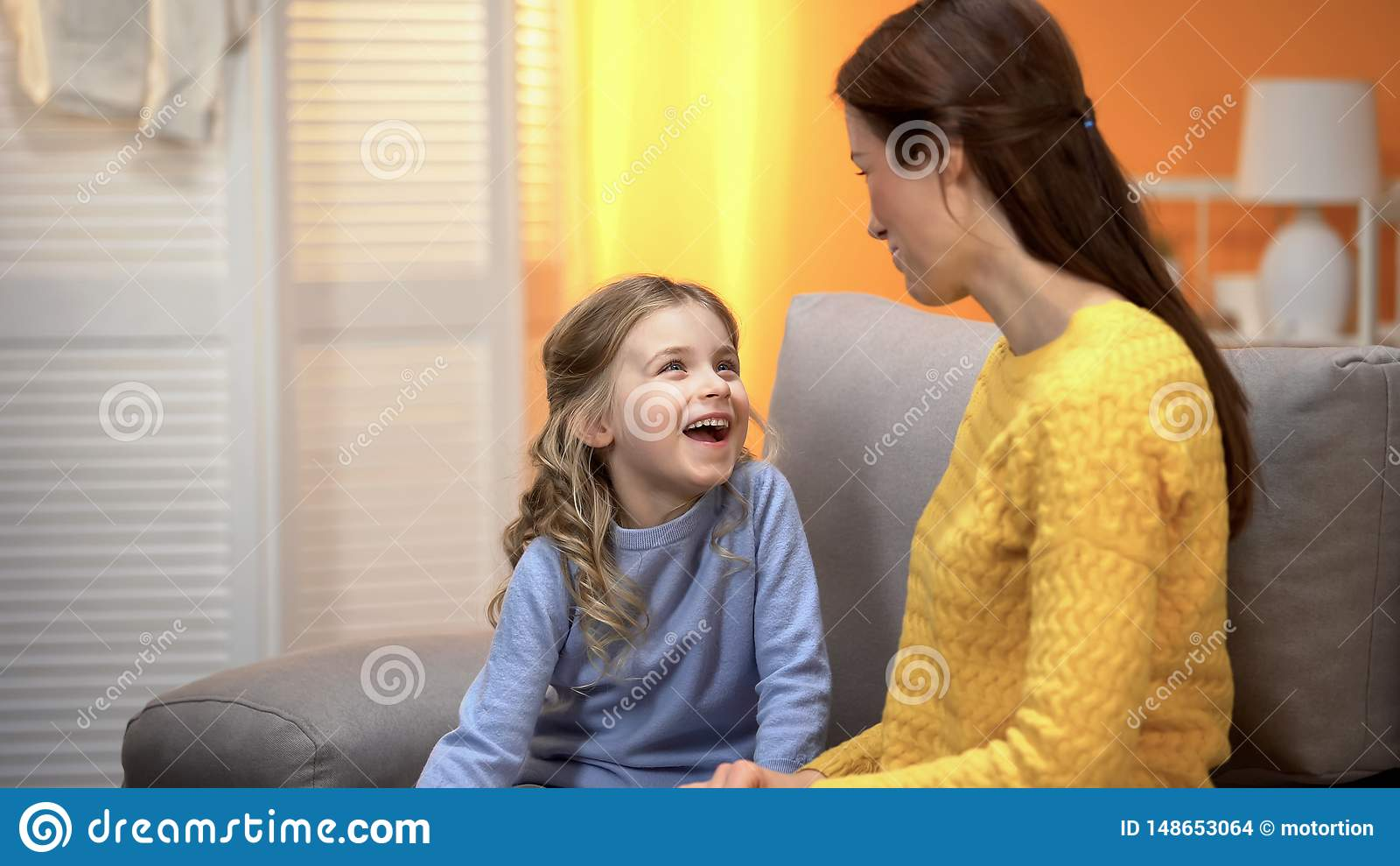 Gelukkige lachende meisjes vertellende glimlachende mama grappige verhalen, vertrouwende relaties