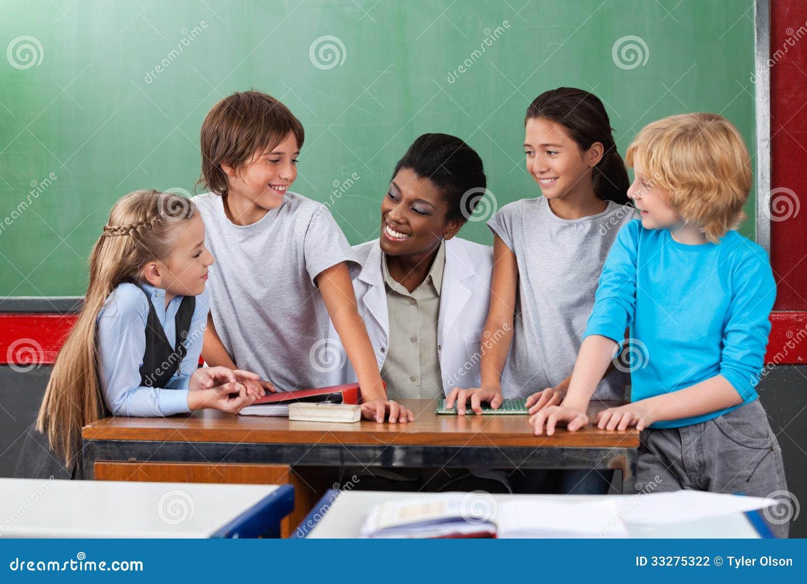 Gelukkige Leraar With Students Communicating bij Bureau