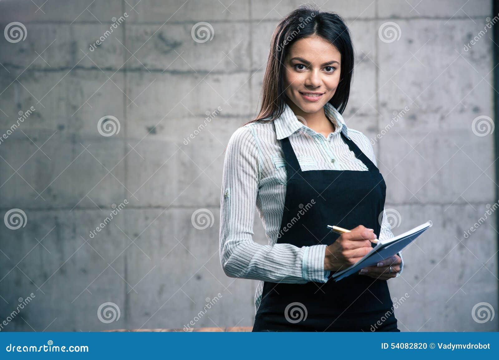Gelukkige leuke vrouwelijke kelner in schort