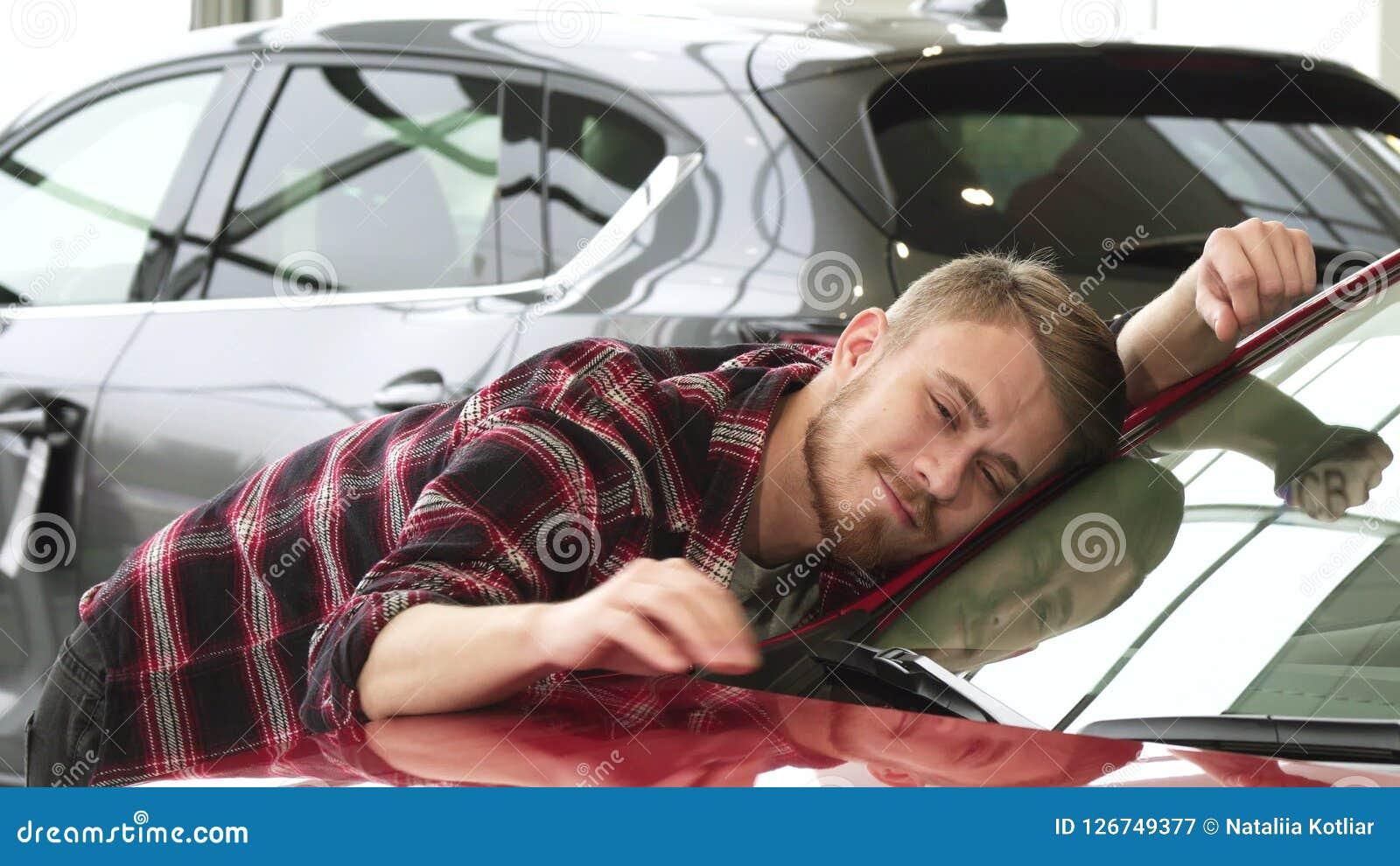 Gelukkige mens die zijn nieuwe auto strijken die zacht tonend duimen bij het handel drijven glimlachen