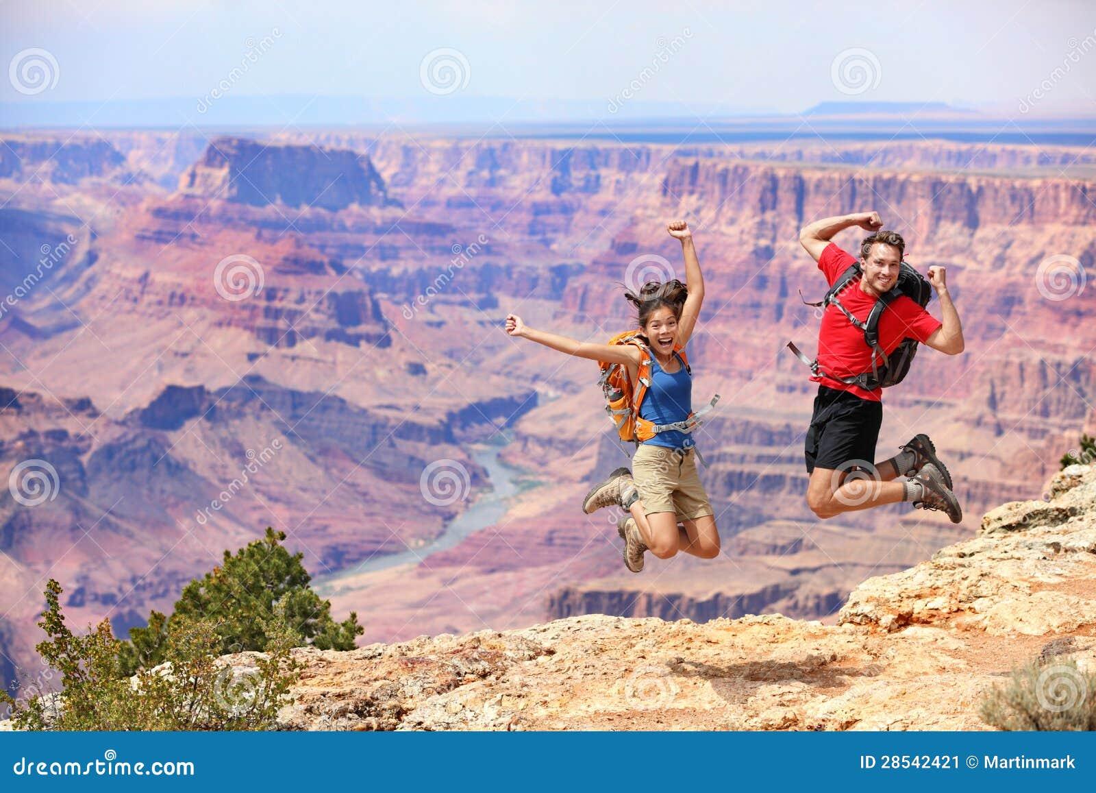 Gelukkige mensen die in Grote Canion springen