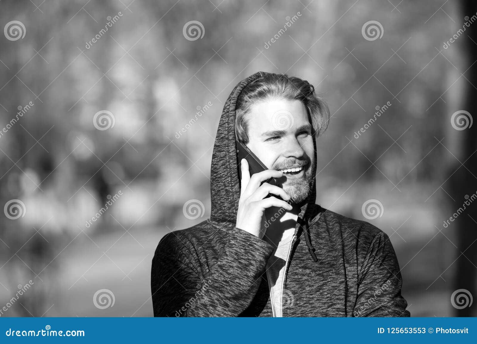 Gelukkige mensenbespreking op mobiele telefoon in park, mededeling