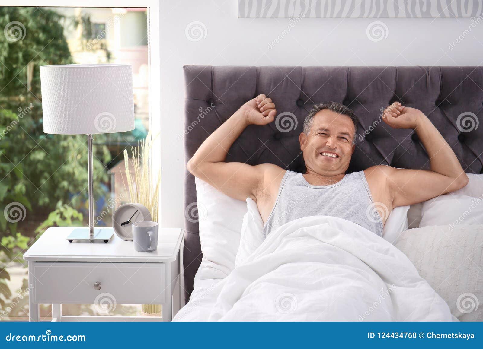 Gelukkige mensenontwaken na het slapen op comfortabel hoofdkussen