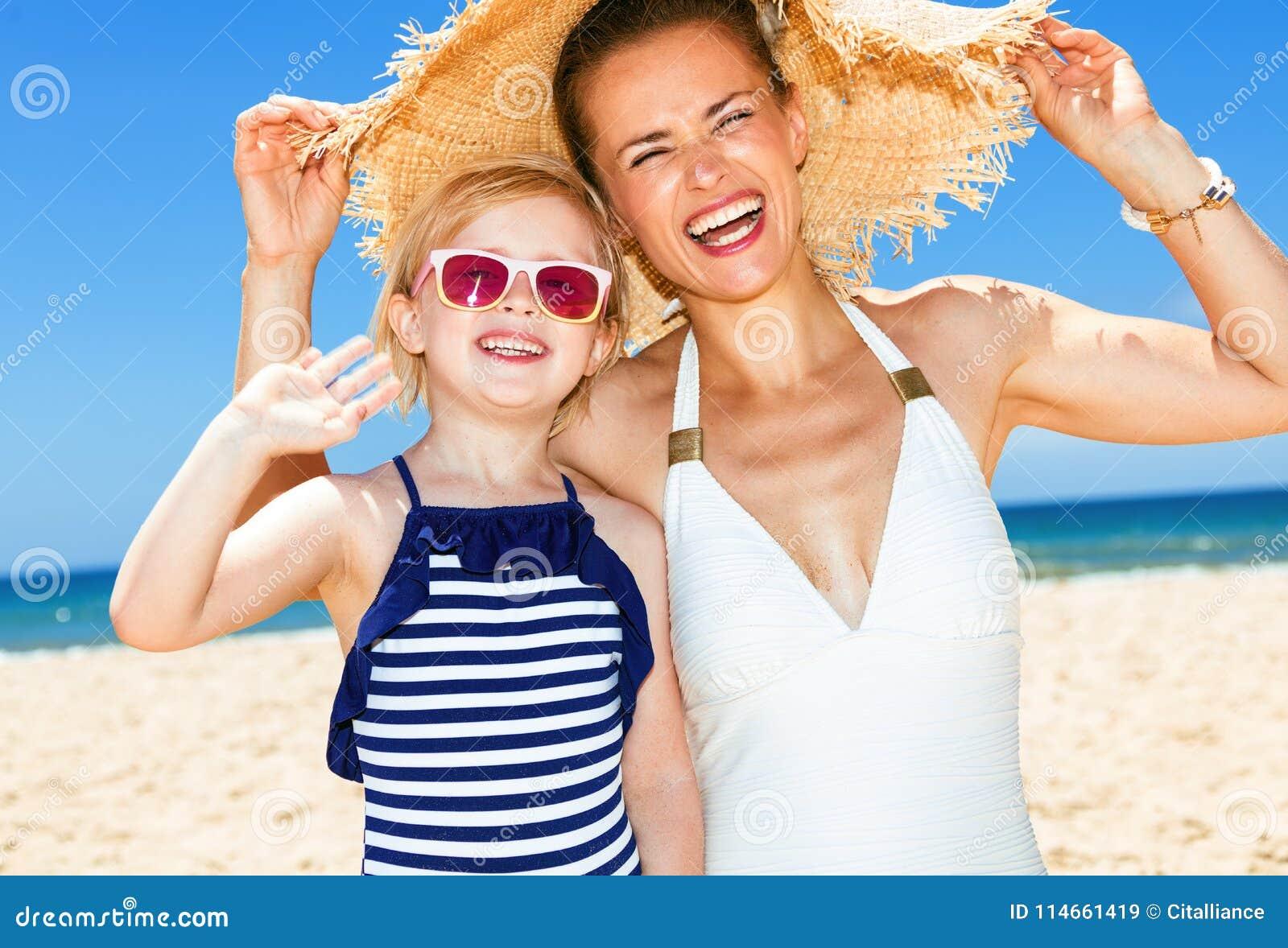 Gelukkige moderne moeder en dochter bij zeekust het handwaving