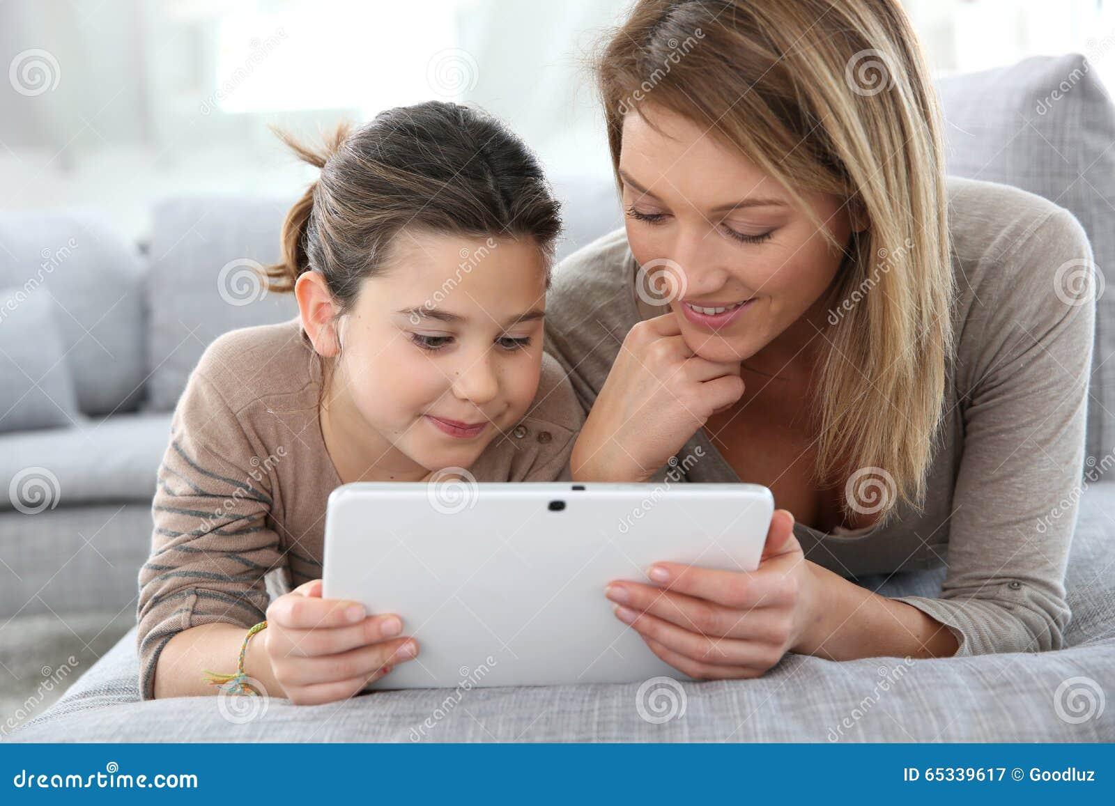 Gelukkige moeder en dochter die tablet gebruiken