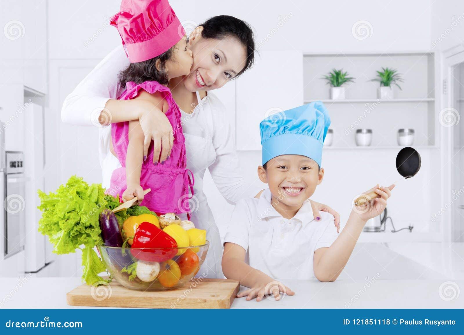 Gelukkige moeder en jonge geitjes met groenten