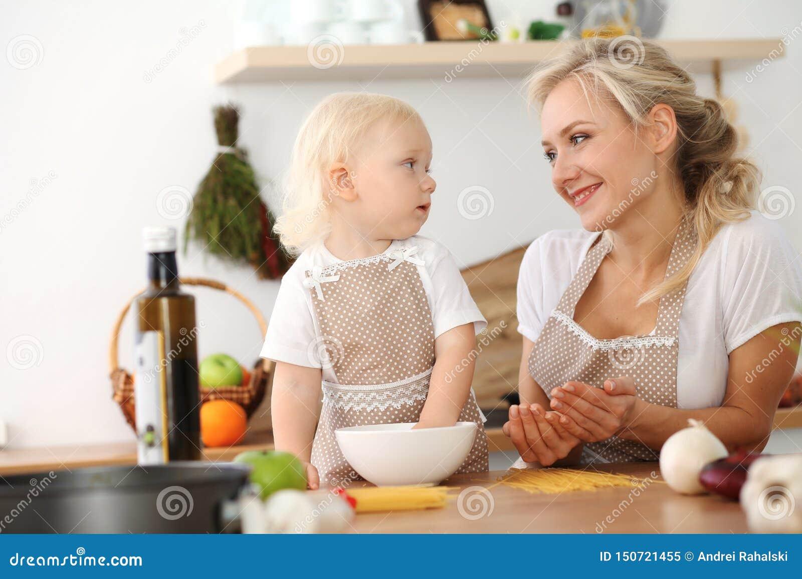 Gelukkige moeder en weinig dochter het koken in keuken Doorbrengend tijd allen samen, het concept van de familiepret