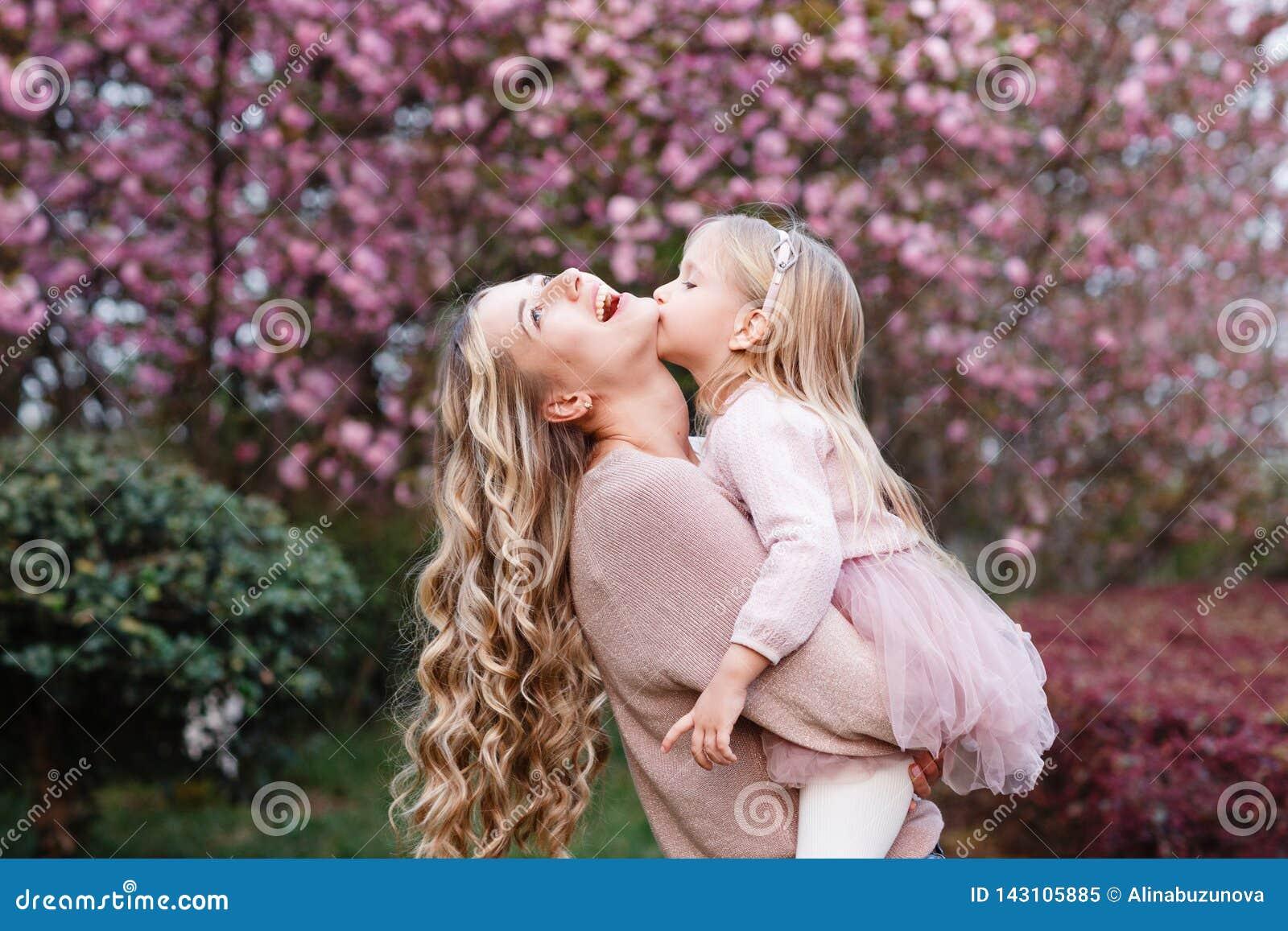 Gelukkige moeder en weinig dochter met lang blondehaar dat in het park omhelst Het concept van de familie De lente, bloeiende bom
