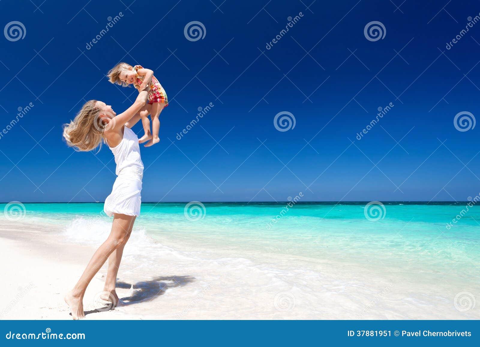 Gelukkige moeder en weinig kind op strand