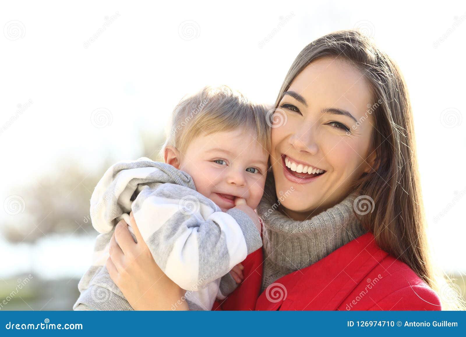 Gelukkige moeder haar zoonsbaby houden die bekijkend u