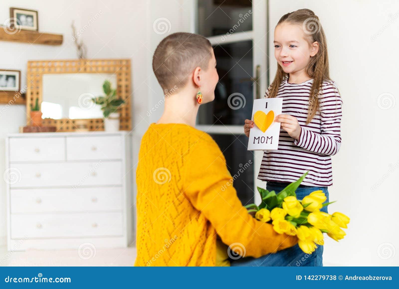 Gelukkige Moederdag of Verjaardagsachtergrond Aanbiddelijk jong meisje die haar mamma met eigengemaakte groetkaart verrassen Fami