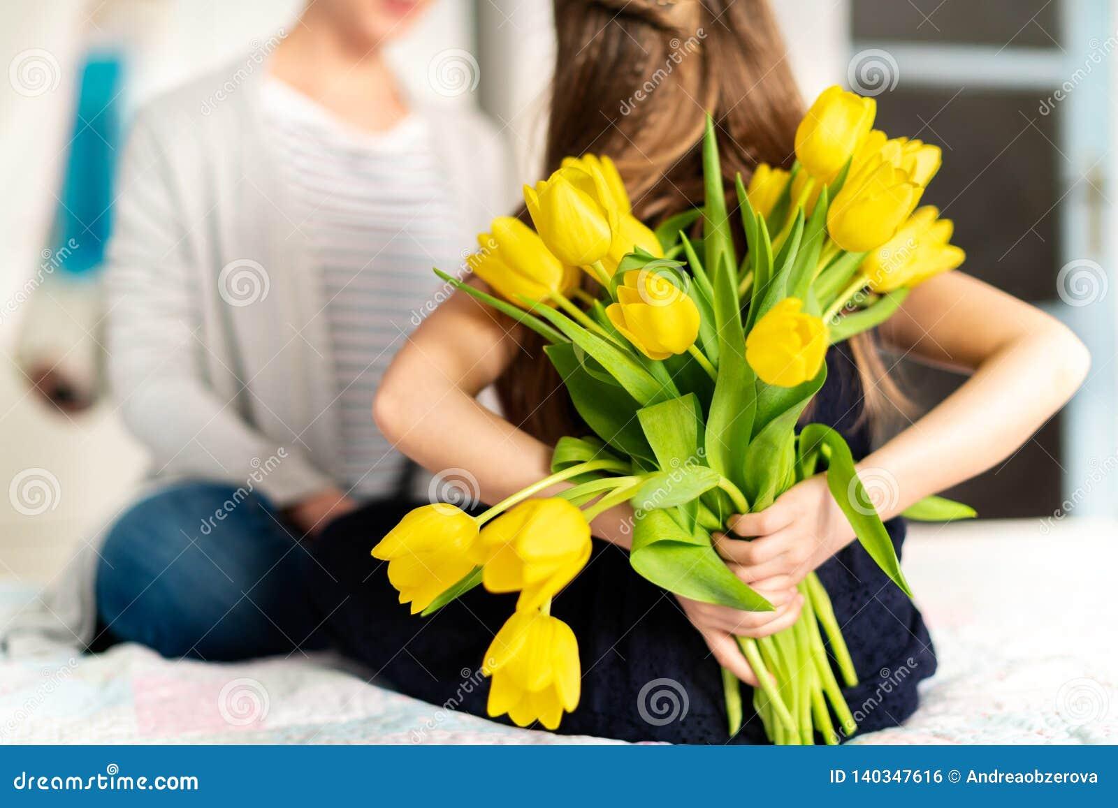 Gelukkige Moederdag of Verjaardagsachtergrond Onherkenbaar jong meisje die haar mamma met boeket van gele tulpen verrassen