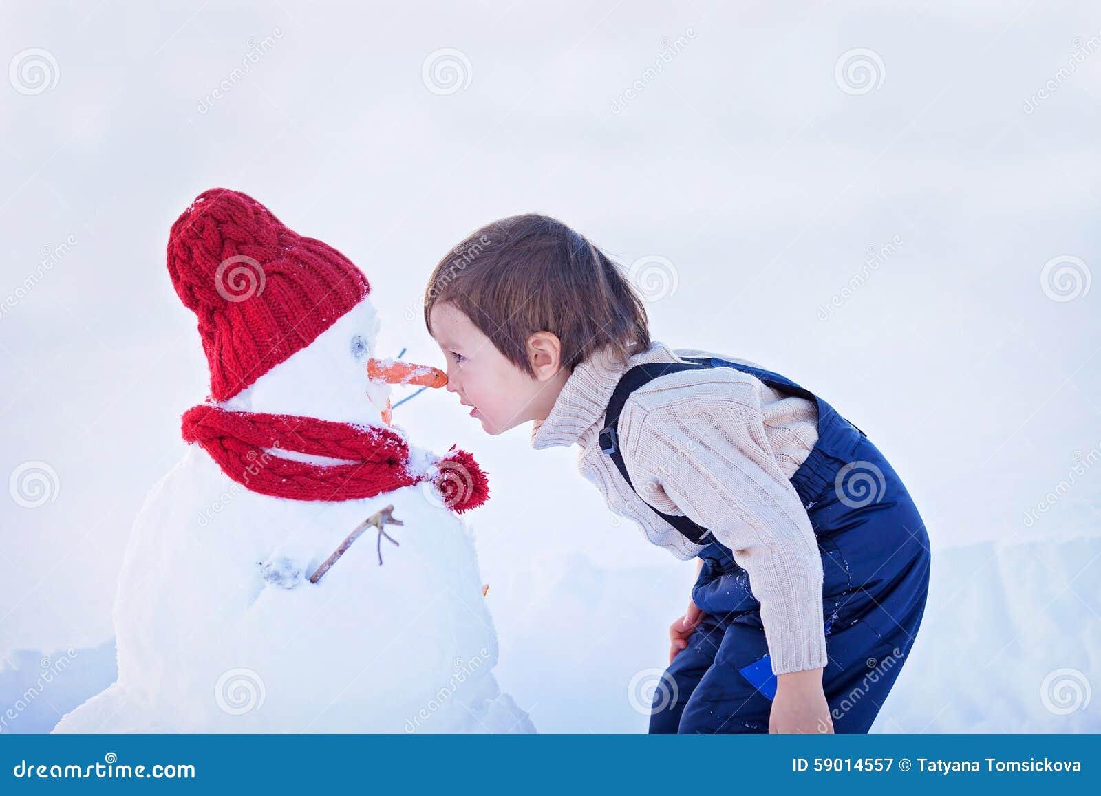 Gelukkige mooie kind bouwsneeuwman in tuin, de winter, neus t