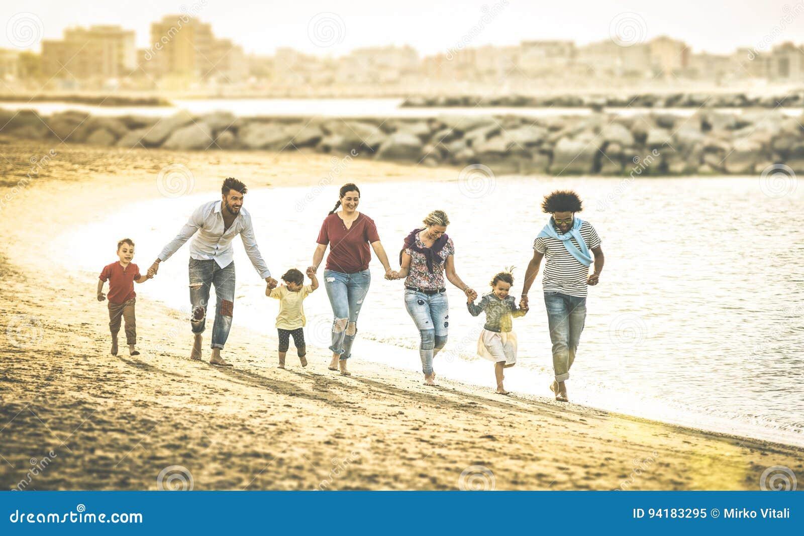 Gelukkige multiraciale families die samen bij strand bij zonsondergang lopen