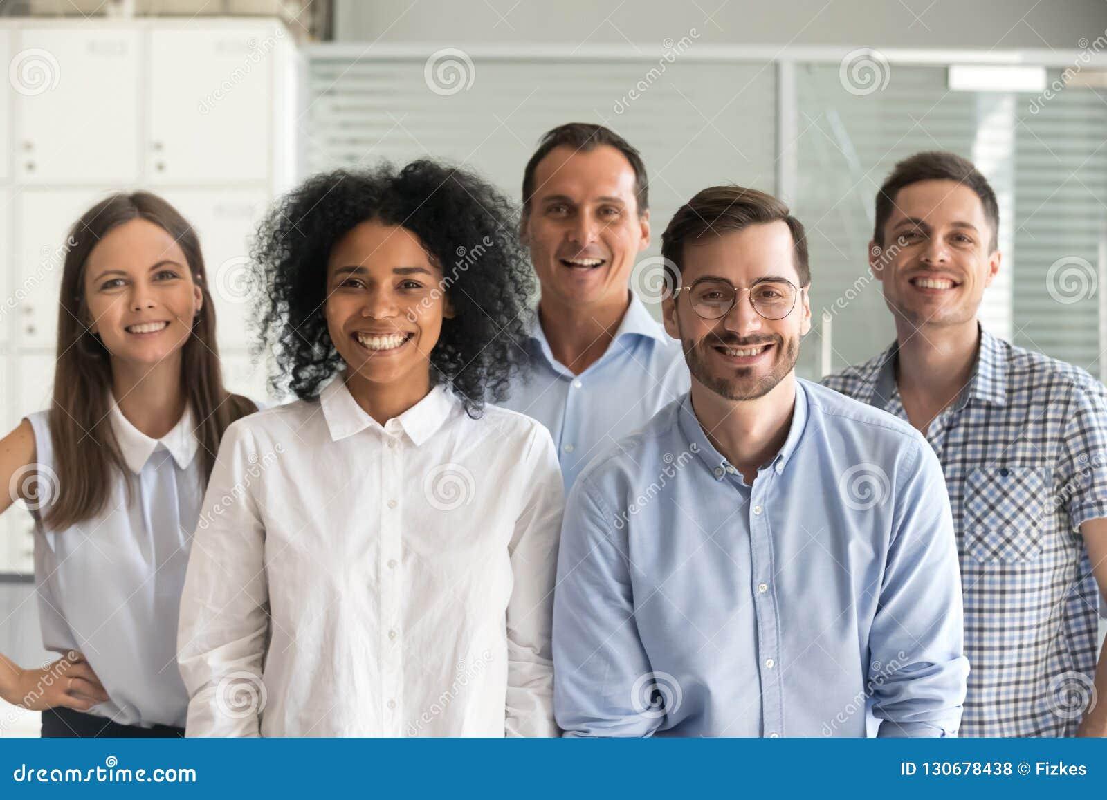 Gelukkige multiraciale professionele werknemers die camera, team bekijken