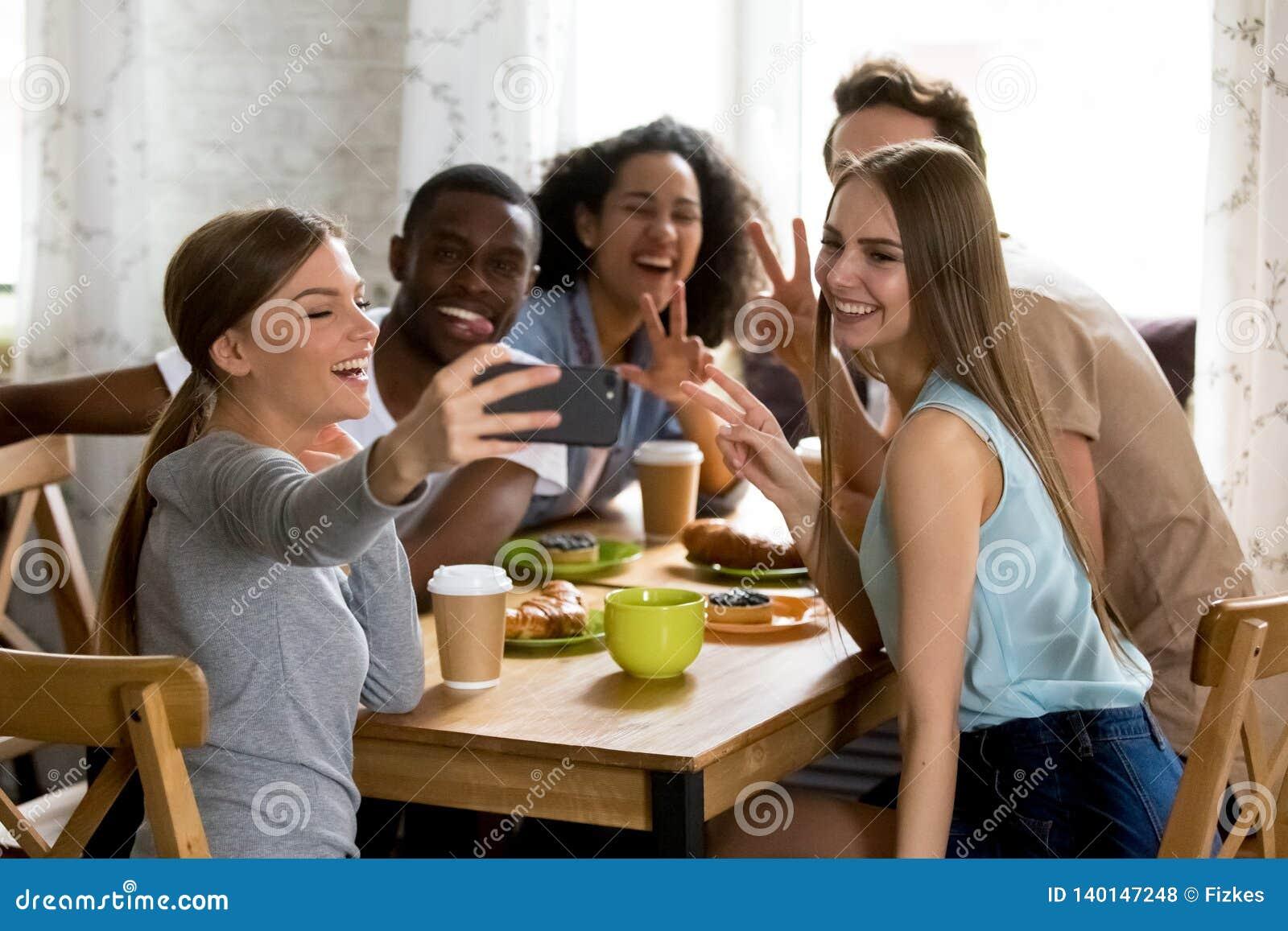 Gelukkige multiraciale vrienden die grappige selfiefoto maken, die video registreren