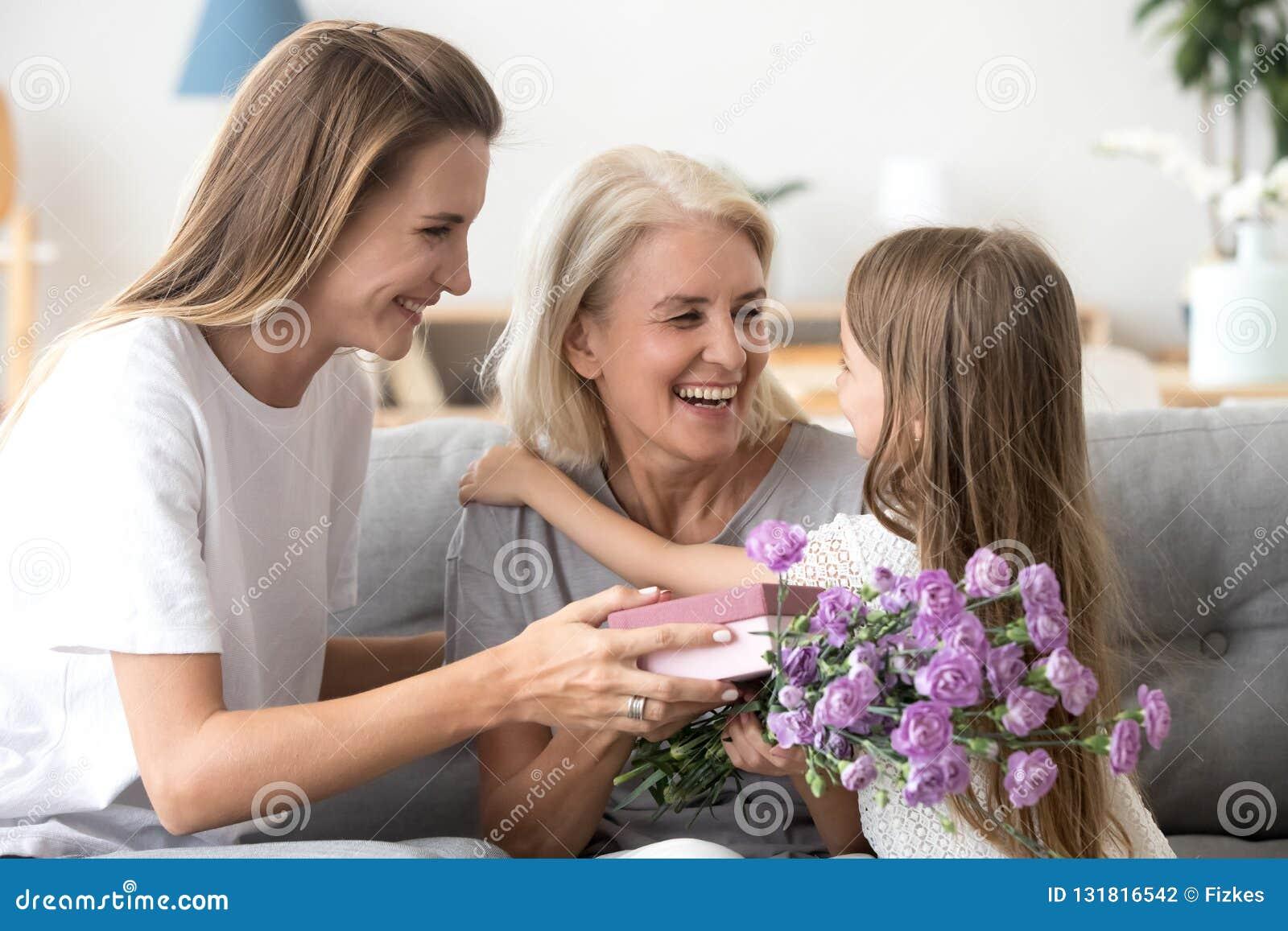 Gelukkige oma die kleinkind en gekweekte dochter danken voor bloemen