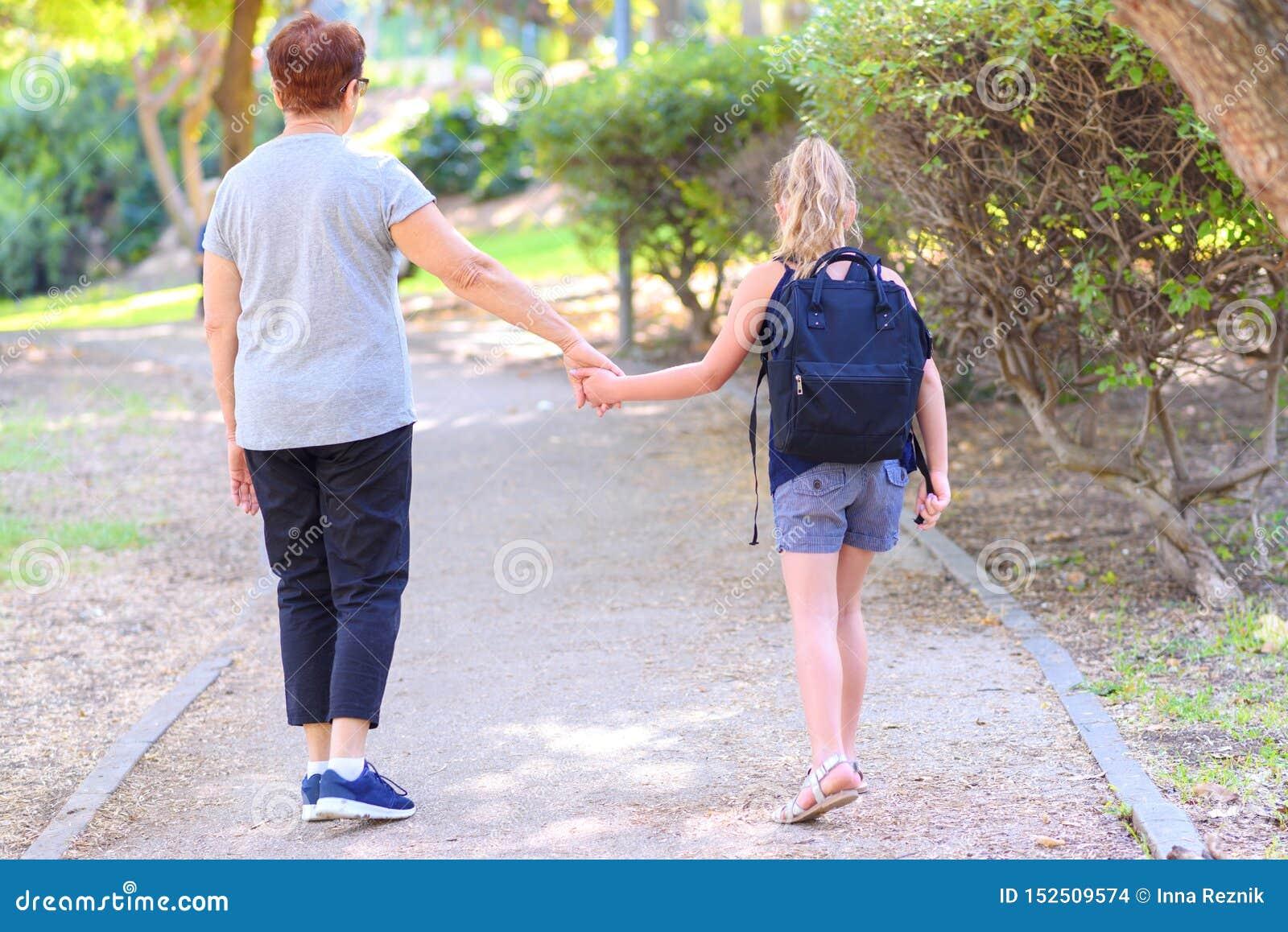 Gelukkige Oma en kleindochter die aan school op de straat in het de herfstpark lopen