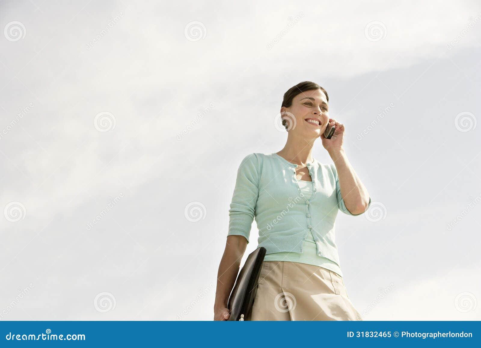 Gelukkige Onderneemster Communicating On Cellphone tegen Bewolkte Sk