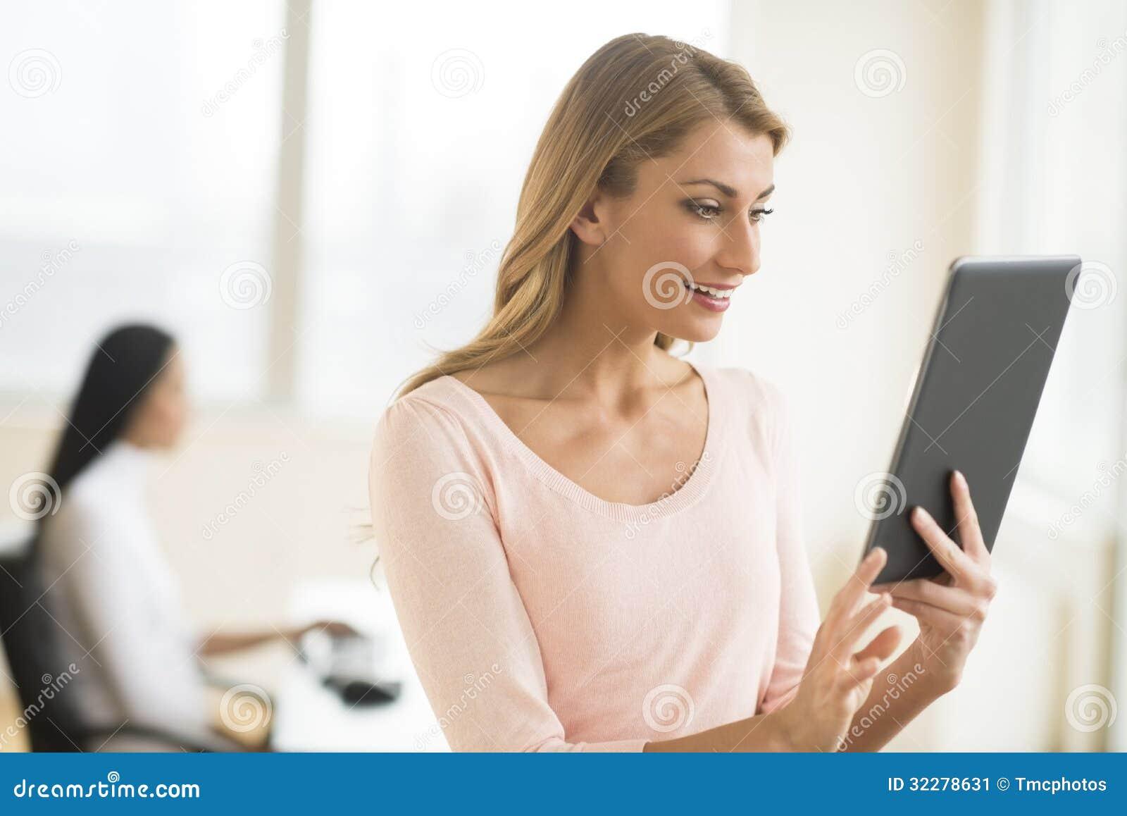 Gelukkige Onderneemster Looking At Touchpad in Bureau