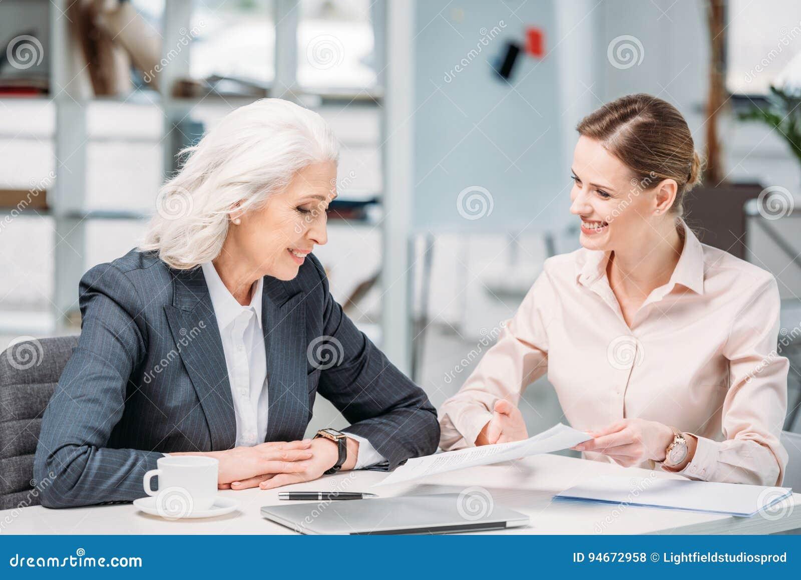 Gelukkige onderneemsters die bedrijfsproject op vergadering in bureau bespreken