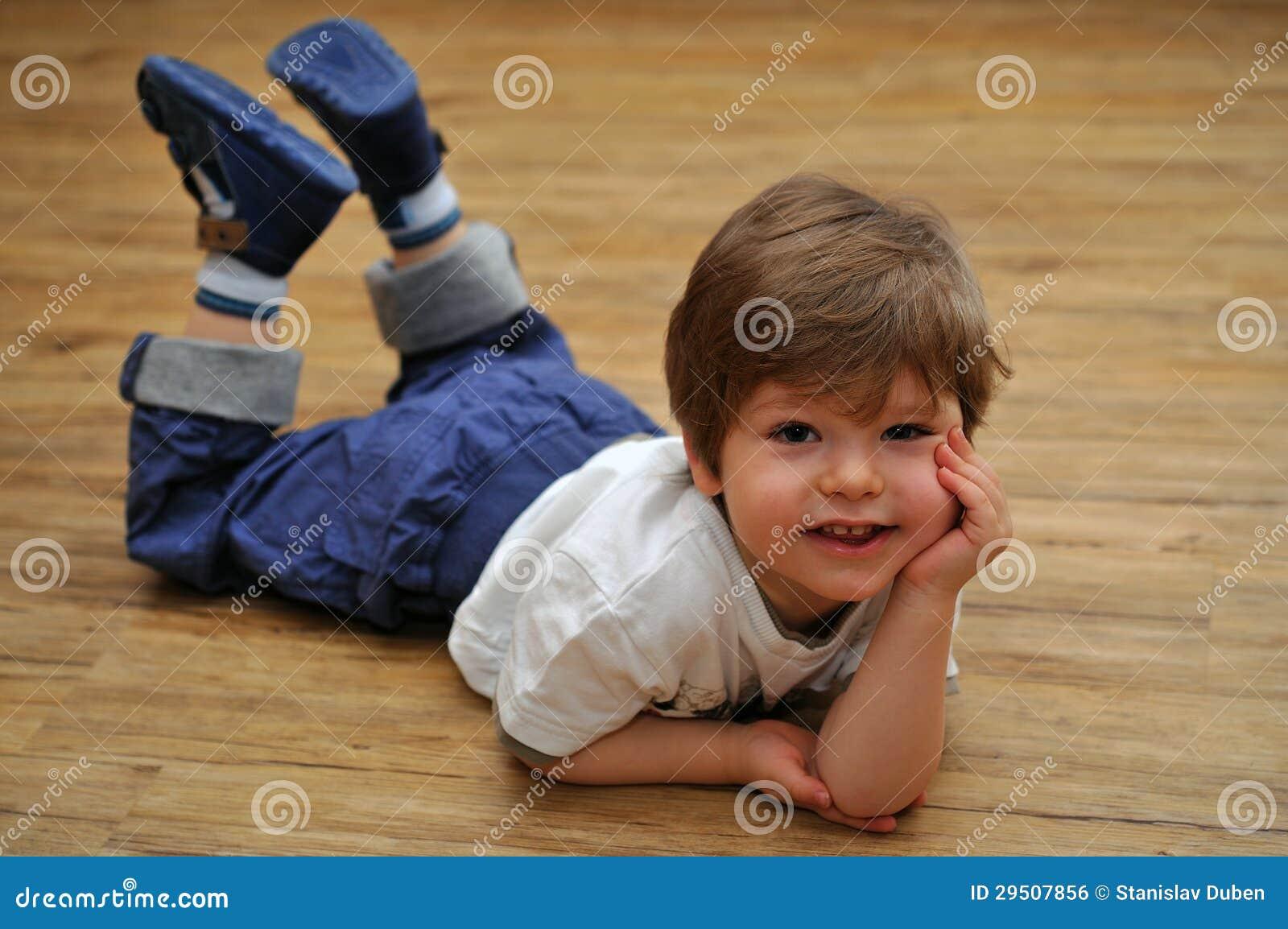 Gelukkige ontspannende kleine jongen die op houten vloer ligt