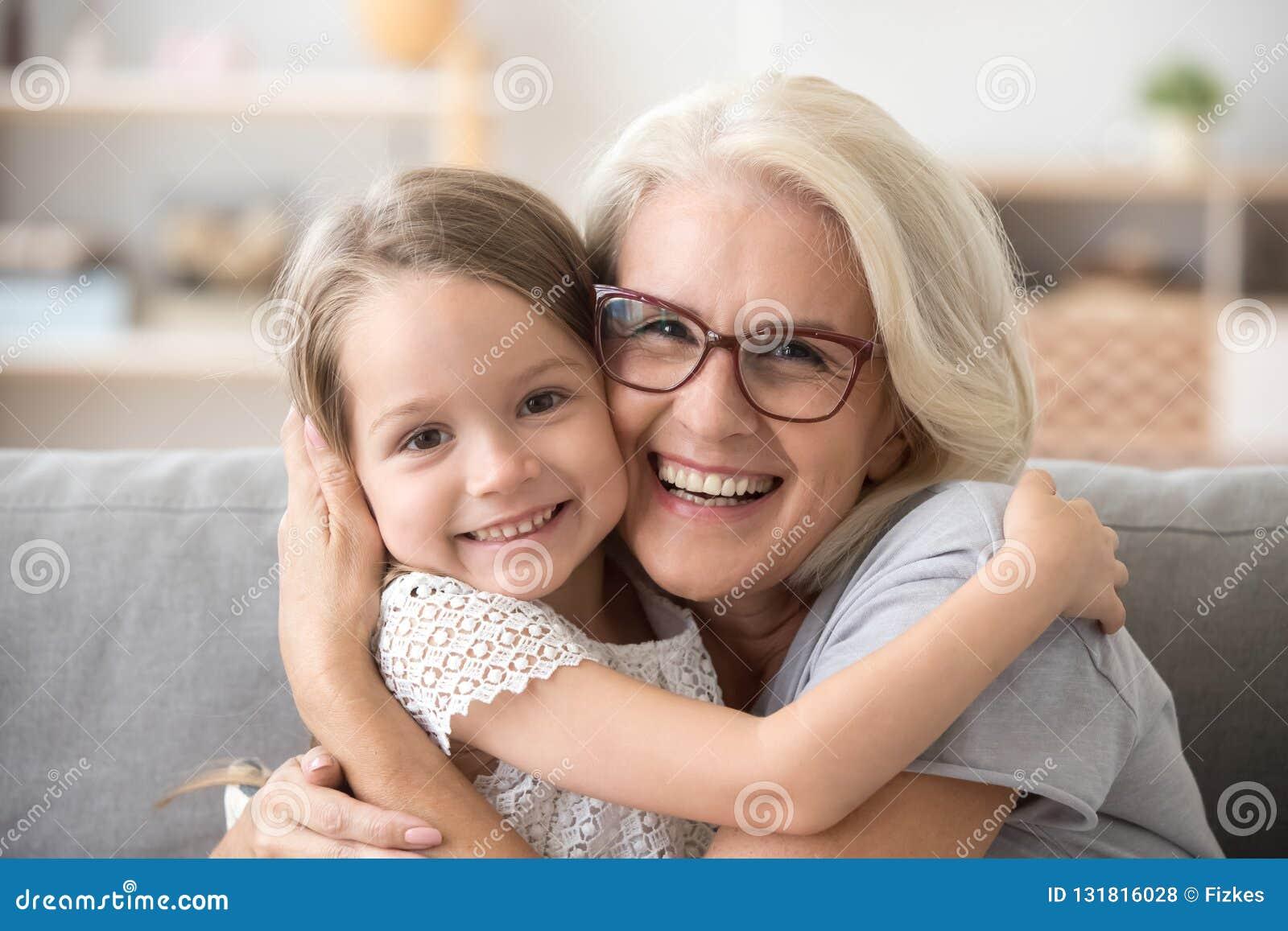 Gelukkige oudere grootmoeder die weinig kleinkindmeisje koesteren die a kijken
