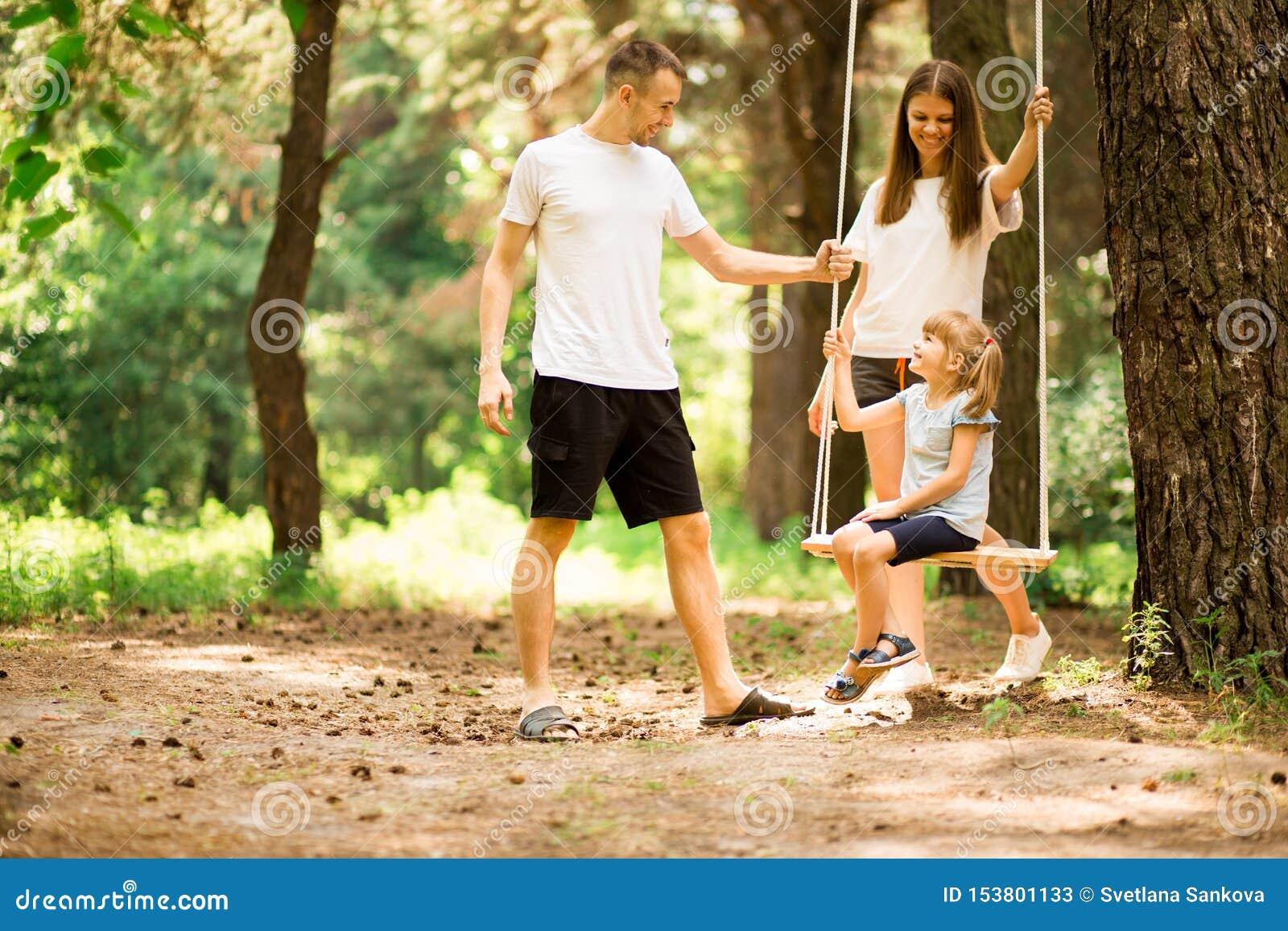 Gelukkige ouders die kindmeisje slingeren bij park