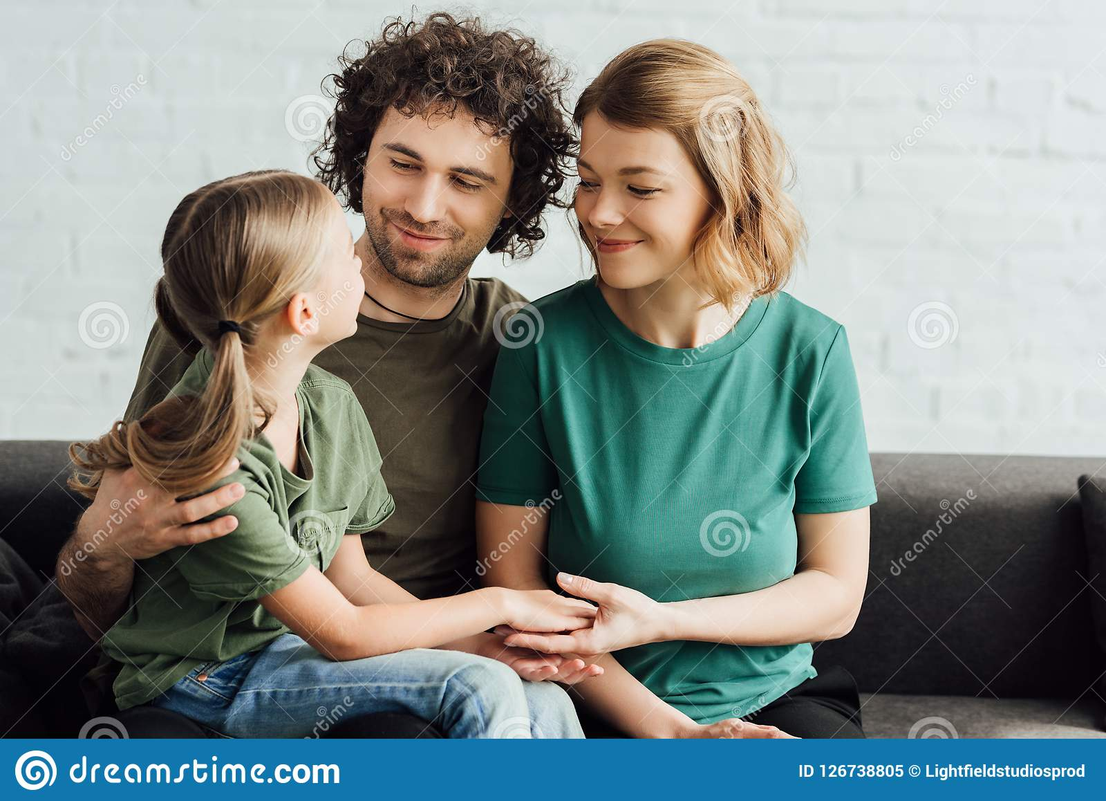 Gelukkige ouders die leuk bekijken weinig dochter terwijl het zitten op laag