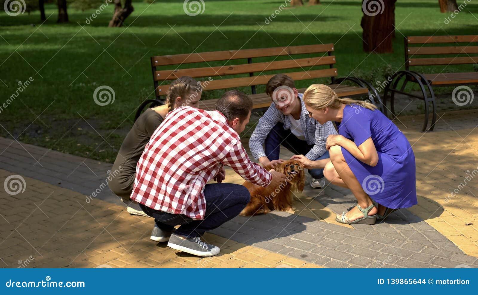 Gelukkige ouders en hun kinderen die mooie hond in park, huisdierengoedkeuring strijken