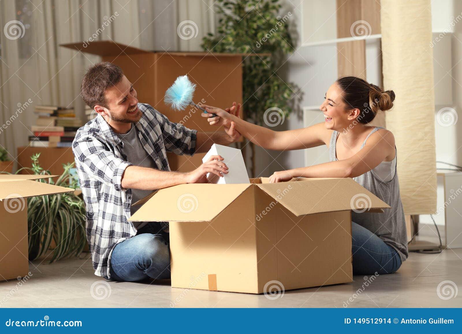 Gelukkige paar het gekscheren unboxing bezittingen die zich naar huis bewegen