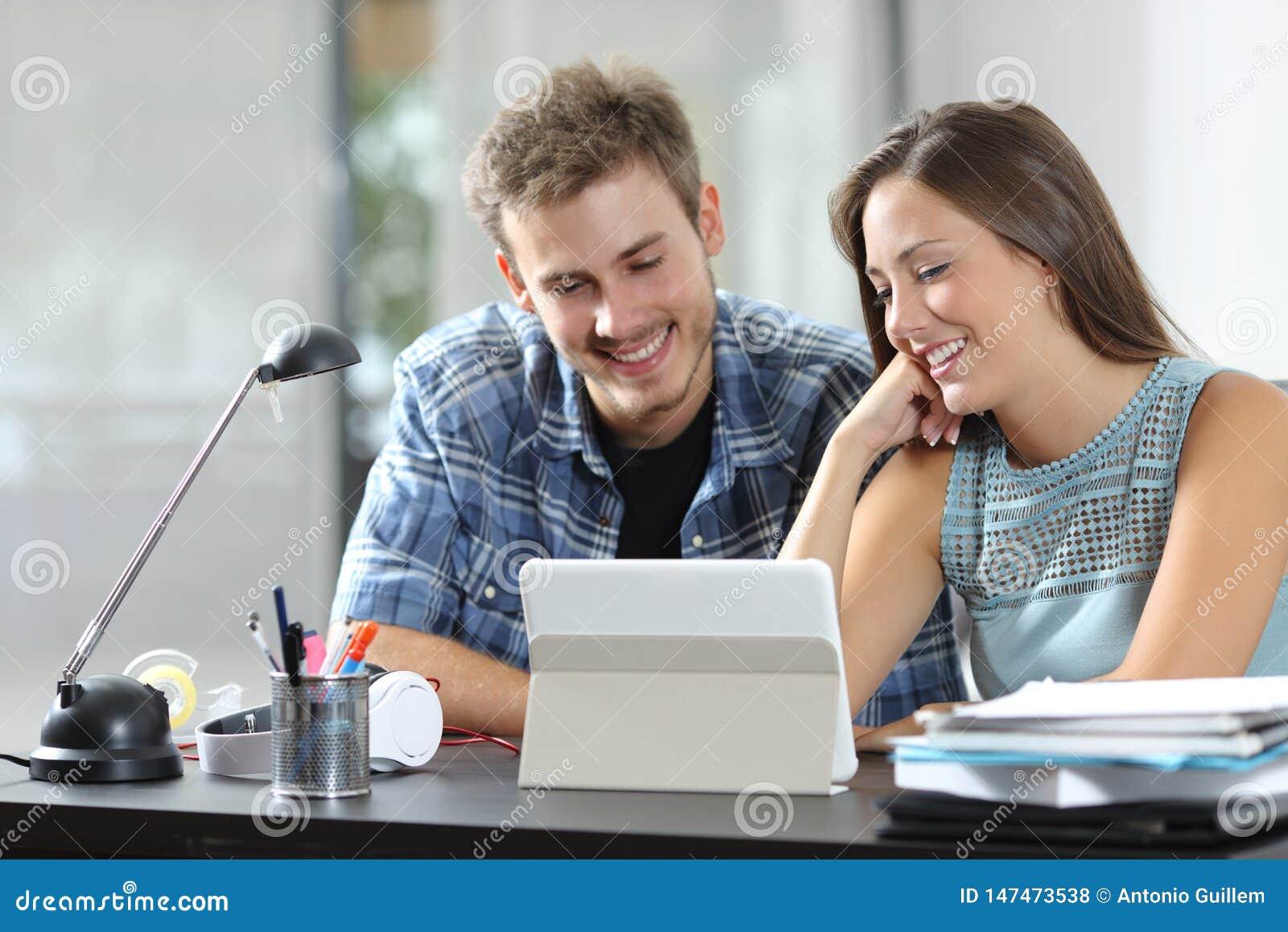 Gelukkige paar het letten op tabletinhoud op een bureau thuis